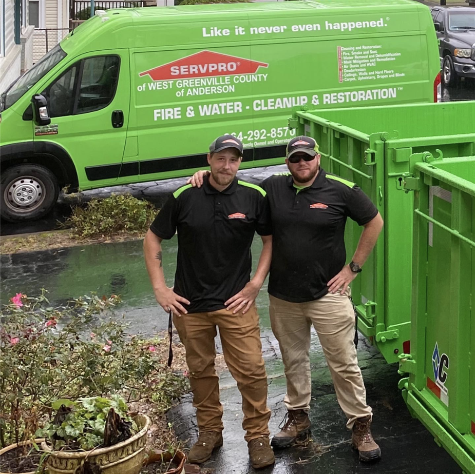 Two production crew members standing outside of SERVPRO green vehicles in SERVPRO shirts