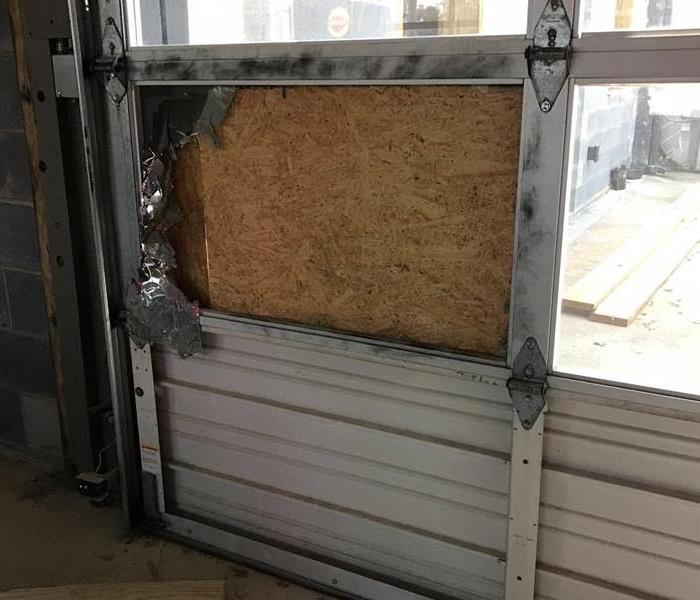 Window that has been broken and boarded up with a piece of wood