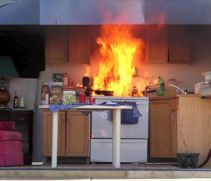 A stove has caught on fire and there is a kitchen fire occurring in the home.